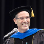 (Dean Christopher Long) Older man with glasses in academic robes with blue trim neck chevron