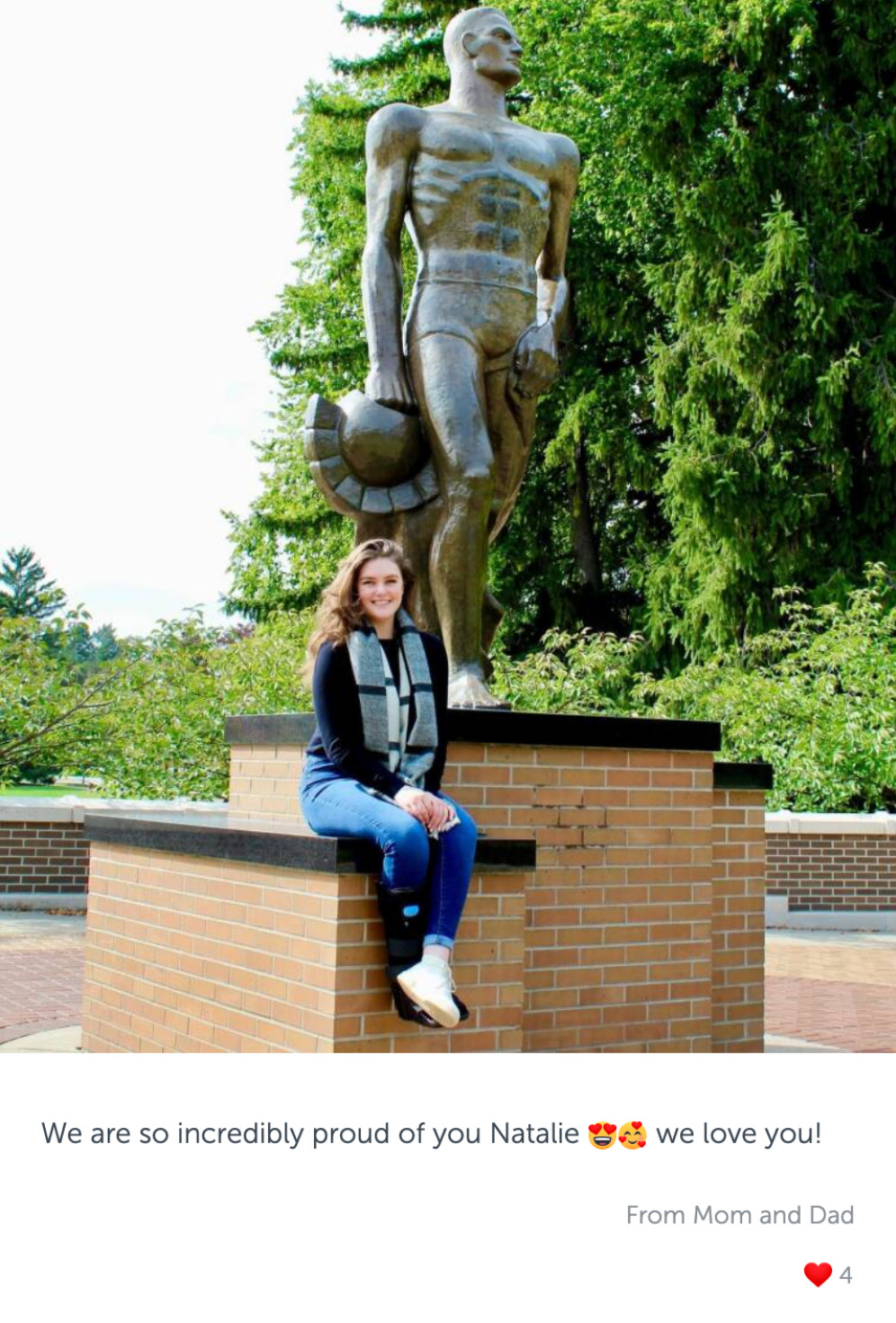 Post with photo of a woman sitting next to Sparty statue, and congratulatory message